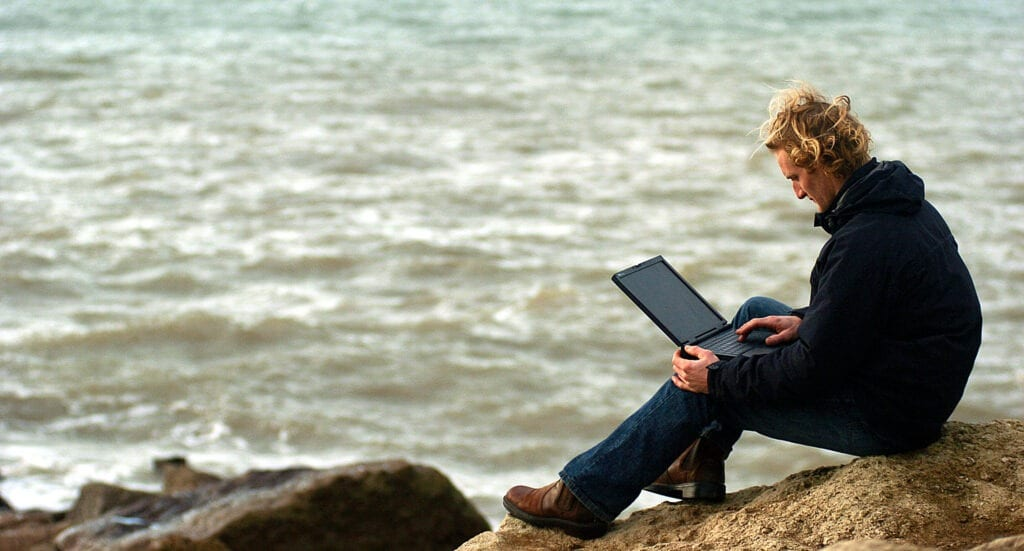 man working away from office sea laptop England