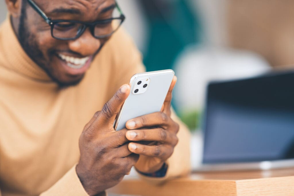 African-American man holding the latest Iphone 11 Pro Max model in silver color, close up