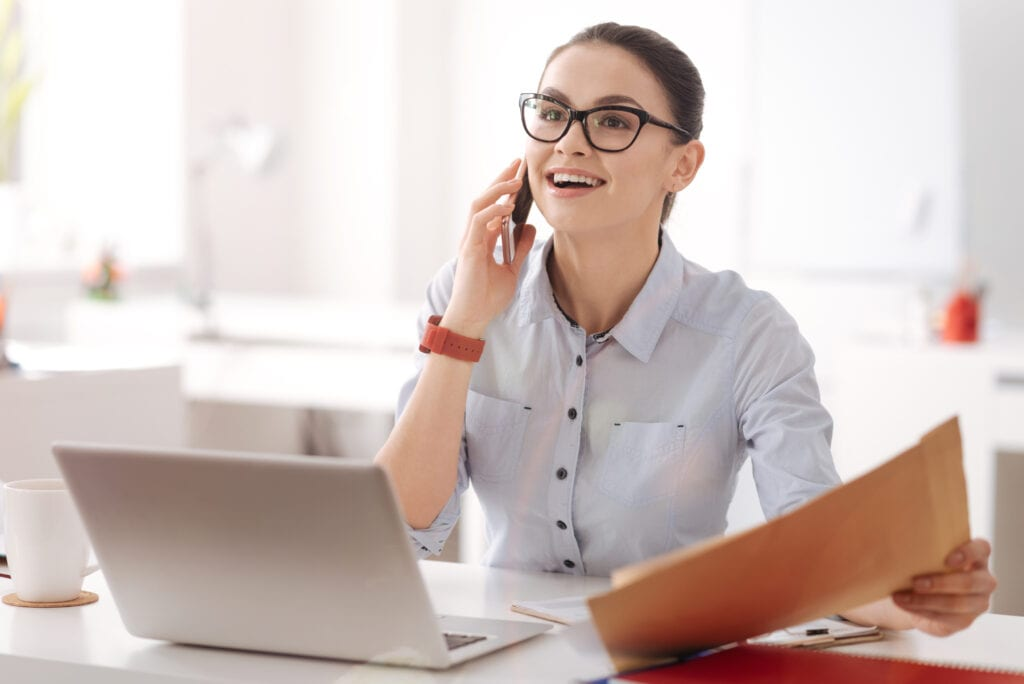 Express positivity. Young businesswoman holding phone near ear wearing glasses while being at workplace